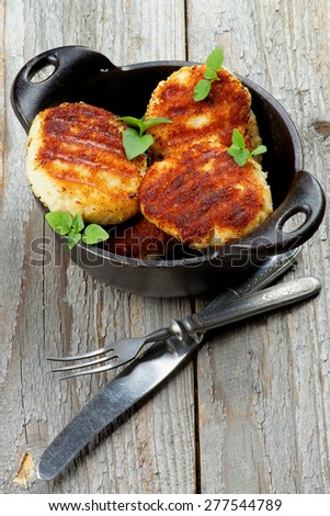 Delicious Homemade Meat Cutlets in Black Saucepan with Fork and Knife closeup on Rustic Wooden background - stock photo