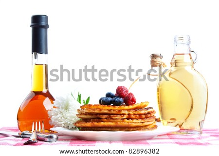 Delicious homemade pancakes with maple syrup and forest fruits, still life. - stock photo