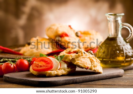 delicious homemade pizza rolls stuffed with tomatoes and mozzarella on wooden table - stock photo