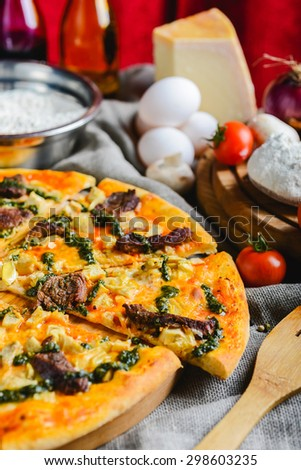 Delicious homemade pizza with cheese meat and mushrooms on a wooden table with a creative decoration tomato cheese eggs and other ingredients. soft focus - stock photo