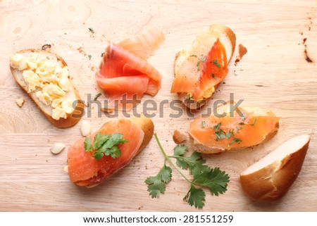 Delicious homemade scrambled eggs with smoked salmon garnished with a fresh parsley leaf on rustic wood