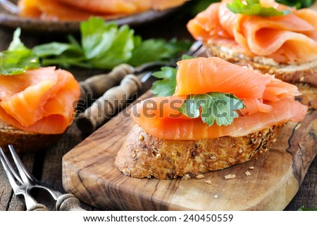 Delicious homemade smoked salmon gluten free canape garnished with a fresh parsley leaf on rustic wood - stock photo