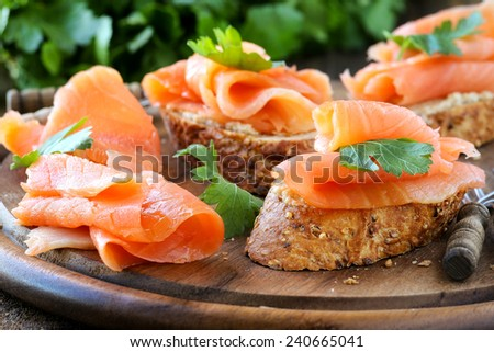 Delicious homemade smoked salmon gluten free canape garnished with a fresh parsley leaf on wood - stock photo