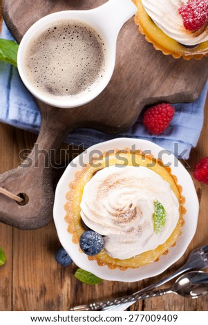 Delicious homemade tartlets served with lemon, lime curd cream, berries and meringue, taken from above on old cutting board.  - stock photo