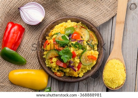 Delicious homemade vegetarian couscous with tomatoes, zucchini, yellow, red, green bell pepper  - stock photo