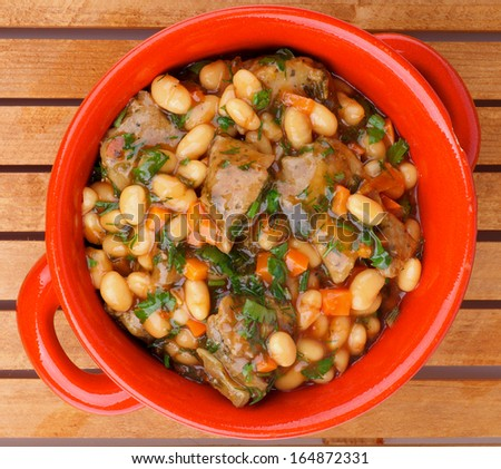Delicious Homemade White Beans Stew with Beef and Greens in Red Pot closeup on Wooden background. Top View - stock photo
