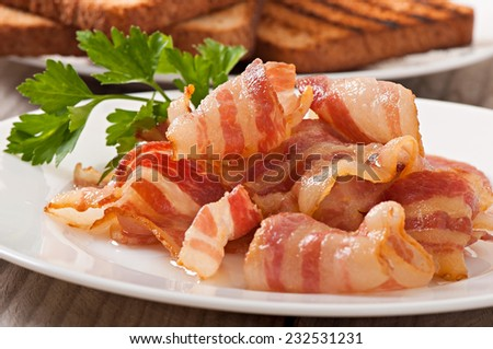 delicious hot fried bacon on a white plate and toast - stock photo