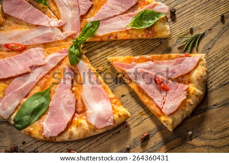 Delicious hot italian pizza with different spices on wooden table ready to eat - stock photo