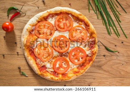Delicious hot italian pizza with tomatoes, cheese and different spices on wooden table ready to eat - stock photo