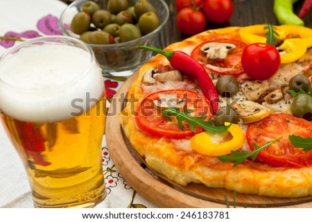 Delicious hot pizza with cold beer - stock photo