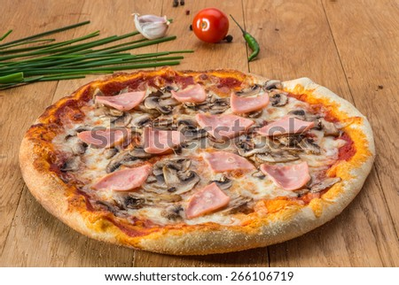 Delicious hot pizza with ham, mushrooms and different spices on wooden table ready to eat - stock photo