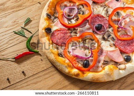 Delicious hot pizza with pepperoni, ham, mushrooms, paprika and different spices on wooden table ready to eat - stock photo