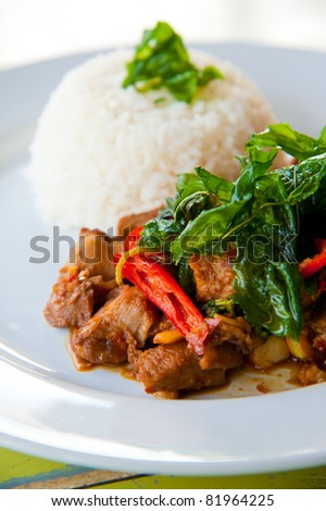 delicious hot rice with fried pork, vegetable and green herbs