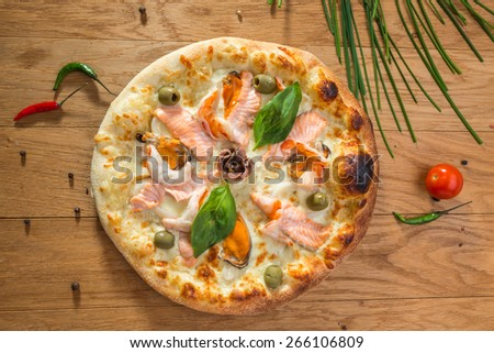 Delicious hot seafood pizza with shrimp, octopus, salmon, olives and different spices on wooden table ready to eat - stock photo