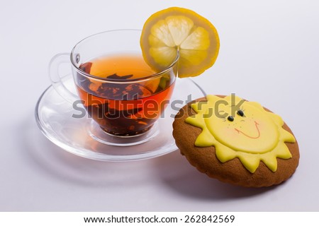Delicious hot tea and cookies in the form of the sun. - stock photo