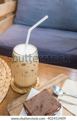 Delicious ice coffee and Chocolate Brownie serve on wooden tray with tissue paper with spoon - stock photo