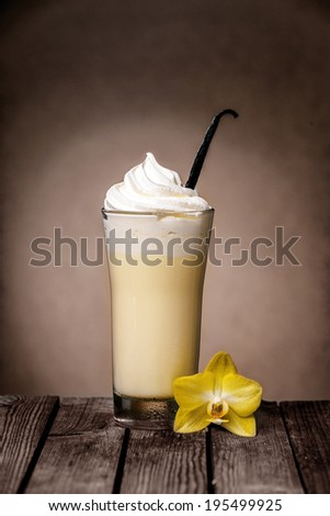 Delicious iced vanilla milkshake topped with cream or ice cream with a vanilla pod for flavoring and flower on a rustic wooden table - stock photo