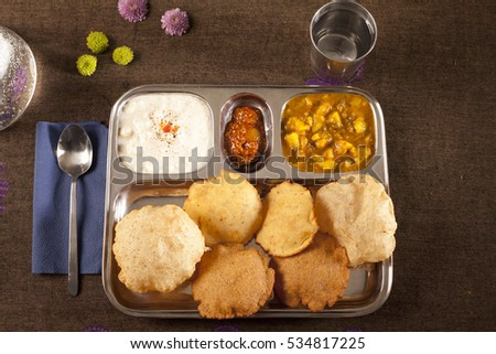 Delicious Indian thali or steel plate with vegetarian meal of puri, sabzi, raita, achar