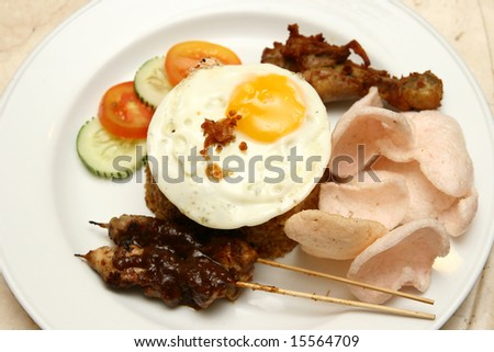 Delicious Indonesian Nasi Goreng with prawn crackers and chicken satay. - stock photo