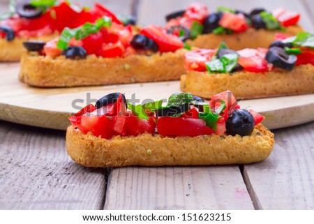 Delicious italian appetizer bruschetta with tomato, olives and basil  - stock photo