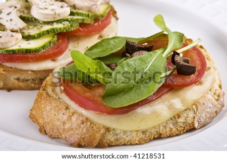 Delicious Italian bruschetta made with mozzarella cheese, tomatoes, arugula, black olives, zucchini and mushrooms on a toasted country bread. - stock photo