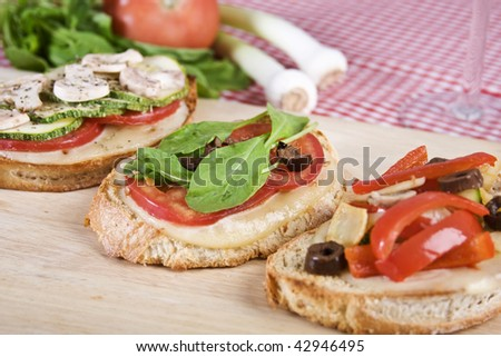 Delicious Italian bruschettas made with mozzarella cheese, tomatoes, arugula, black olives, zucchini, mushrooms, red pepper, fennel and olives on a toasted country bread. - stock photo