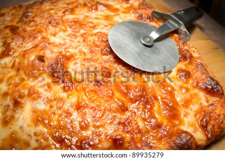 Delicious Italian cheese pizza on a cutting board with slicer
