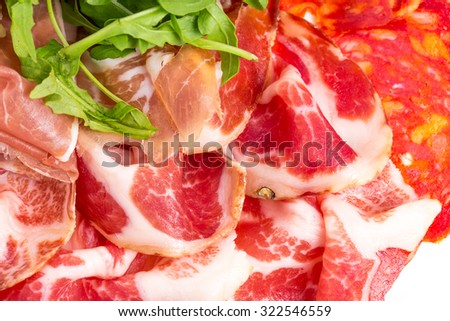 Delicious italian dried meat with heap of arugula. Macro. Photo can be used as a whole background. - stock photo