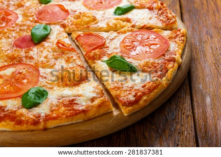 Delicious italian Margherita pizza decorated with basil leaves - thin pastry crust at wooden background - stock photo