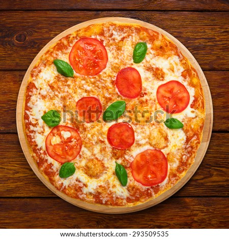 Delicious italian Margherita pizza with tomatoes and mozarella - thin pastry crust at wooden table background, above view on wooden desk - stock photo