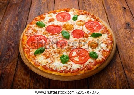 Delicious italian Margherita pizza with tomatoes and mozarella - thin pastry crust at wooden table background on wooden desk - stock photo