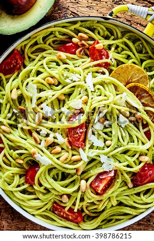 Delicious Italian pasta appetizer with avocado pear, fresh tomatoes, pine nuts and parmesan cheese in a close up overhead view in a pan - stock photo