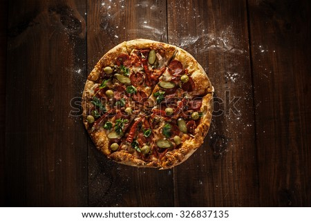 delicious italian pizza served on wooden table top view - stock photo