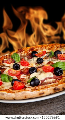 Delicious italian pizza served on wooden table with flames on background