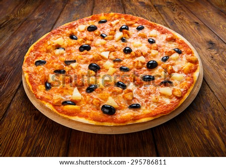 Delicious italian pizza with pineapple, chicken and black olives - thin pastry crust at wooden table background on wooden desk - stock photo