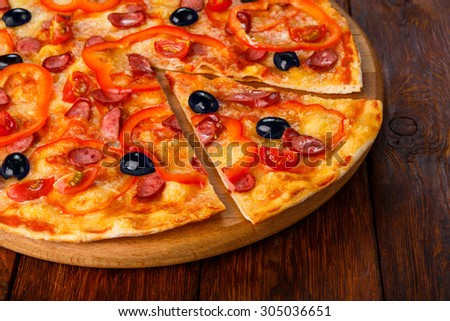 Delicious italian pizza with sausages, peppers, cherry tomatoes and black olives - thin pastry crust piece cut, closeup on wooden round desk at wooden background