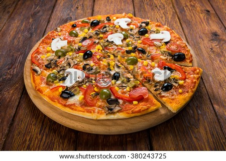 Delicious italian vegetarian pizza with tomatoes, mushrooms, peppers, corn and black olives - thin pastry crust at wooden table background - stock photo