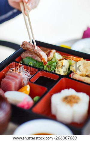 Delicious Japanese lunch bento box with rice, fish sashimi, omelet, meat and vegetables - stock photo