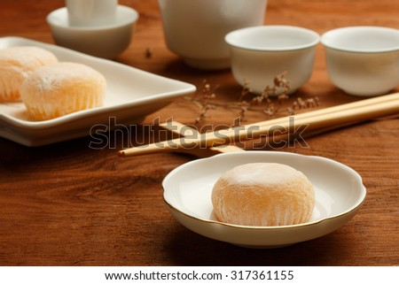 Delicious japanese mochi rice cakes on white plates standing on brown wooden surface with white porcelain cups and bamboo chopsticks. Shallow dof. Focus on cake on foreground. - stock photo