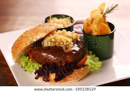 Delicious juicy beef burger with caramelised onions and salad served with potato wedges on a white plate on a wooden table. - stock photo