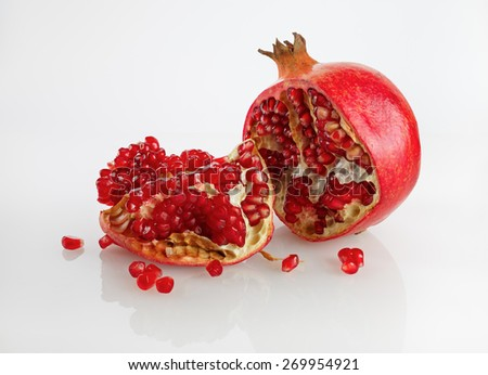 Delicious juicy ripe pomegranate and its half. Studio shot. - stock photo