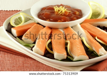 delicious king crab appetizer with hot sauce garnished with lemon zest and spinach - stock photo