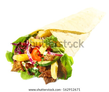 Delicious Lahmacun or tortilla filled with meat, fried potato chips and fresh mixed leafy green salad on a white background - stock photo