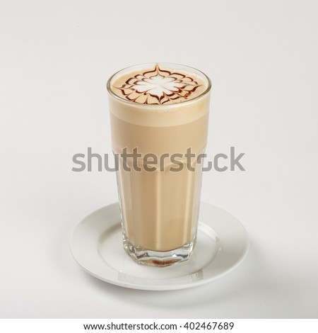 Delicious latte in a tall glass on the plate on white background. Close up side view.