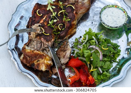 Delicious leg of lamb carved with rosemary and ready to serve. - stock photo