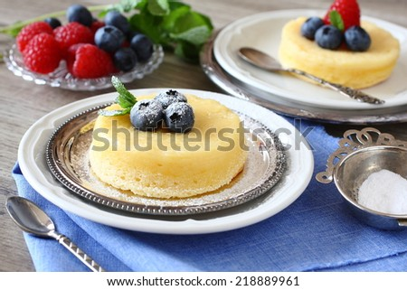 Delicious lemon pudding cake served with berries - stock photo