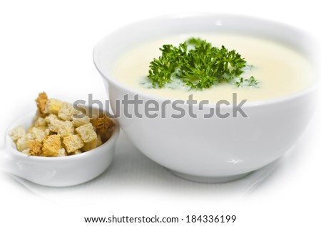 delicious light cream soup with parsley and bread crumbs isolated on white background - stock photo