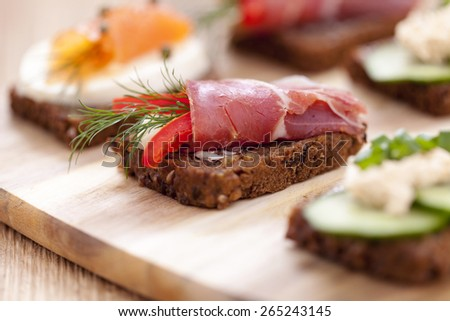 Delicious little sandwiches with tuna, cheese, prosciutto and vegetables. Zoom and macro shots made dSLR camera - stock photo