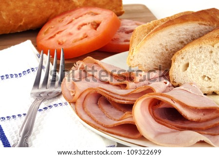 Delicious lunch time spread with ham, bread, cheese and tomatoes with silver fork - stock photo