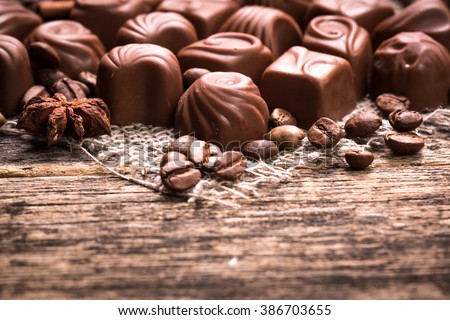 Delicious luxury chocolate candies on wooden background - stock photo